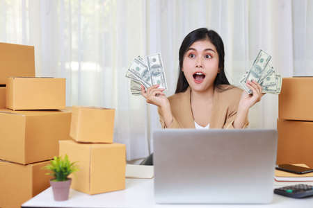 Young asian smart and happy woman in casual dress showing banknote with exciting emotion and working on computer for online purchase shopping order and box packaging on table (new normal concept)