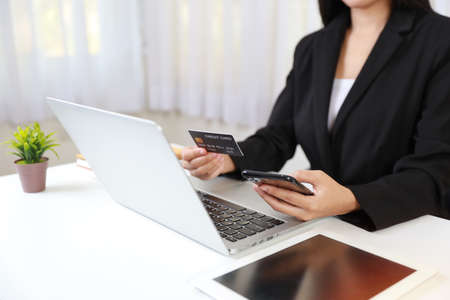 Woman hands sitting and holding smartphone and using computer  and tablet with credit card for online payment or shopping online. Business woman using internet while working. E-Banking concept Stockfoto