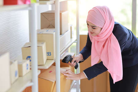 Active asian muslim woman wearing suit holding scanner with package box delivery. Startup small business SME freelance girl work at home concept. Stockfoto