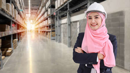 Asian muslim worker woman portrait standing in suit with confident and looking at camera with large warehouse background Stockfoto