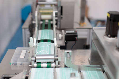 Industry and factory concept, medical face mask production line.