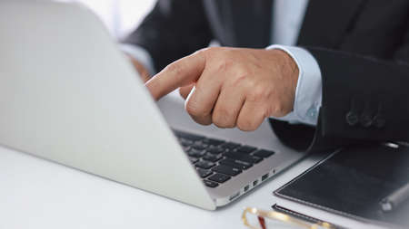 Man hands in black suit sitting and using computer for online payment or shopping online. Business man touching monitor while working. E-Banking concept Stockfoto