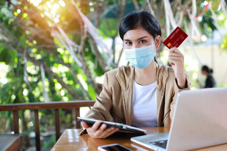 Young asian woman with protect mask for healthcare, sitting in coffee shop and using on smartphone and working on laptop computer and showing credit card. New normal and social distancing concept Stockfoto