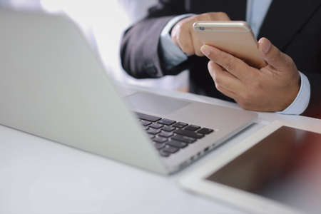 Man hands in black suit sitting and using computer for online payment or shopping online. Business man using mobile phone while working. E-Banking concept Stockfoto