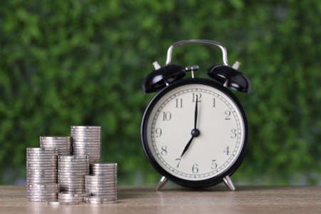 Business investment and saving growth for advertising concept. Stacking coin growing with clock on wood table and green nature background, meaning of tax or earning money