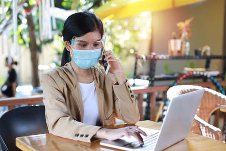 Young asian woman hands in casual dress with protect mask for healthcare, sitting in coffee shop and using on smartphone and working on laptop computer. New normal and social distancing concept Stockfoto
