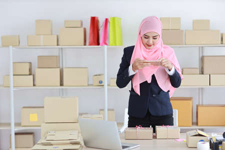 Religious asian muslim woman in blue suit standing and taking picture of package box deliver from mobile phone. Startup small business SME freelance girl work at home with happy smiling face