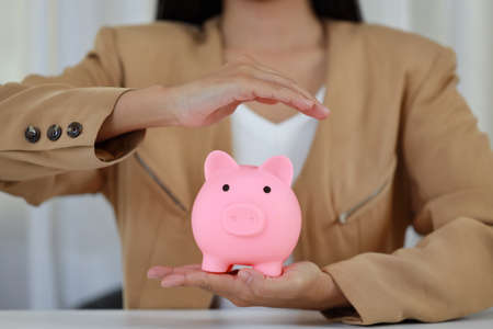 Young active business woman hands in casual dress sitting and protecting piggy bank on white table. Insurance and security concept