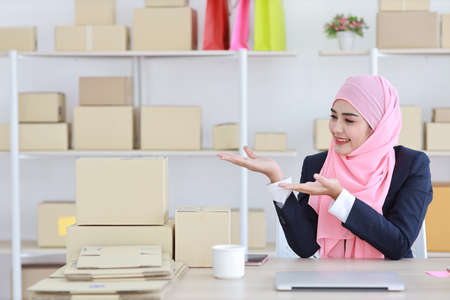 Religious asian muslim woman in blue suit and pink shaft on head sitting and using computer with confidence and showing something on hand with business package SME box delivery background.