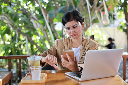 Young asian woman in casual dress with face shield for healthcare, sitting in coffee shop and using on smartphone and working on laptop computer and showing dislike