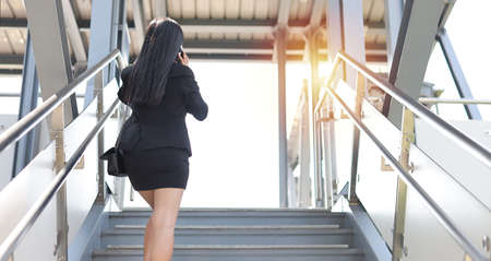 Rear view asian business woman in business black suit with protect mask for healthcare walking on footbridge public outdoor and using smartphone. New normal and social distancing concept