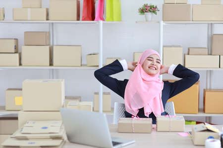 Religious asian muslim woman in blue suit and pink shaft sitting with happiness and relaxation emotion. Business woman sit with package SME box delivery background. Work at home concept