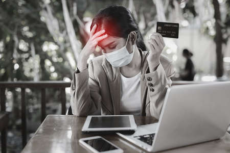Young asian woman hands in casual dress with protect mask for healthcare, sitting in coffee shop and using tablet and working on laptop computer and showing credit card with unhappy emotion Stockfoto
