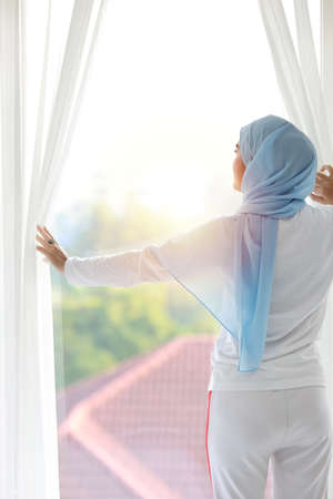 Rear view beautiful asian muslim woman wearing white sleepwear, stretching her arms after getting up in the morning at sunrise. Cute young girl with blue hijab standing and relaxing while looking away Stockfoto