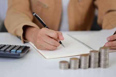 Smart and active asian businesswoman hands writing something on notebook with saving growth on stacking coin on table, meaning of earning money or investment or tax for business advertising concept