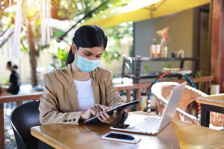 Young asian woman hands in casual dress with protect mask for healthcare, sitting in coffee shop and using tablet and working on laptop computer. New normal and social distancing concept