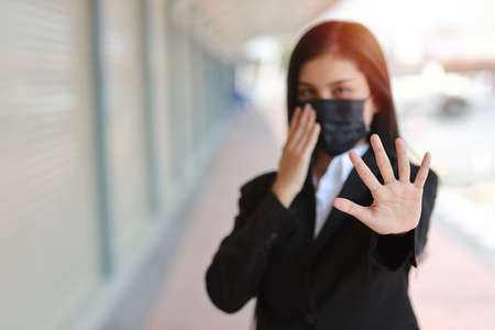 Young asian business woman in business suit with protect mask for healthcare walking on street public outdoor and making stop crossing hands gesture for stop corona virus outbreak. New normal concept