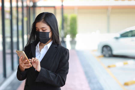 Young asian business woman in business black suit with protect mask for healthcare walking on public outdoor and using smartphone. New normal and social distancing concept Stockfoto