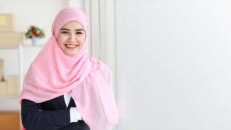 Religious asian muslim woman in blue suit and pink shaft on head standing and looking at camera with confidence. Business woman stand with package SME box delivery background. Work at home concept