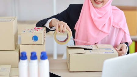 Closeup active asian muslim woman hands in blue suit sitting and working on online package box delivery. Startup small business SME freelance girl working on computer and mobile phone with happy face
