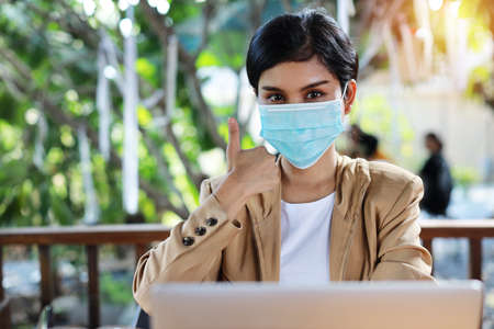 Young asian woman hands in casual dress with protect mask for healthcare, sitting in coffee shop and using on smartphone and working on laptop computer and showing thumb up symbol