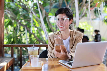 Young asian woman in casual dress with face shield for healthcare, sitting in coffee shop and using on smartphone and working on laptop computer. New normal and social distancing concept