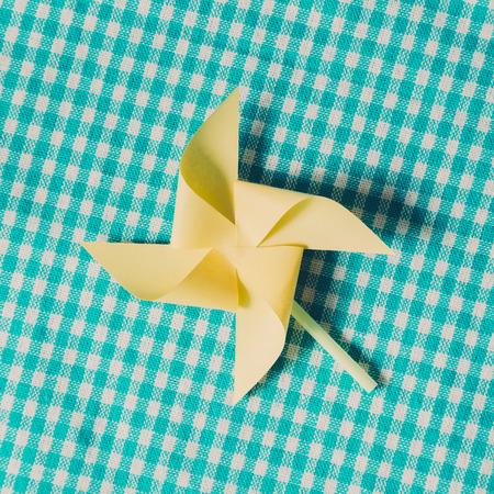Yellow paper pinwheel on blue check fabric background Stock Photo