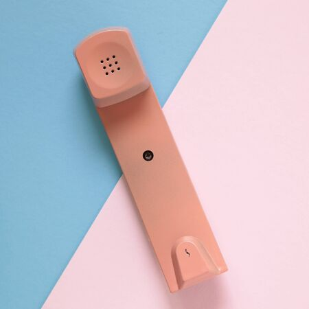 Pink telephone receiver on pink and blue background