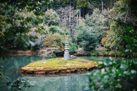 Lake and stone pagoda in Kinkakuji (Golden Pavilion), Kyoto, Japan