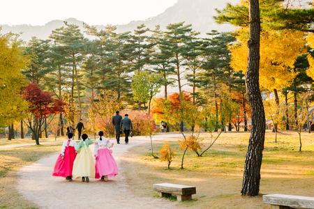 Seoul, Korea - November 9, 2016: Girls with Hanbok (traditional Korean dress) and maple in Gyeongbokgung palace