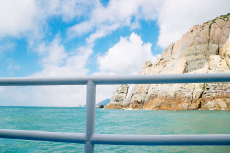 Emerald sea and Haegeumgang Island cliff from cruise boat in Geoje, Korea Stock Photo