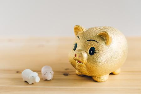 Golden piggy bank on wooden desk
