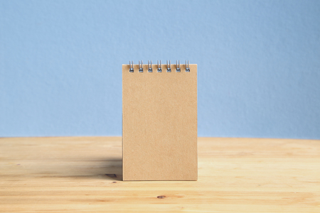 Brown notepad on wooden desk. Office or school daily note paper