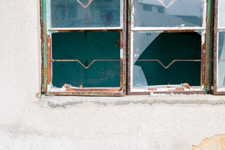 Broken window glass and old wall Stock Photo