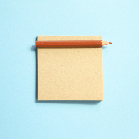 Memo note pad and brown colored pencil on blue background
