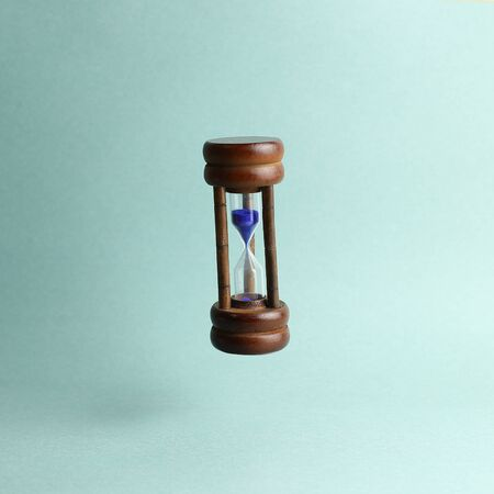 Hourglass floating on green background. Business deadline, last second or time out concept 版權商用圖片