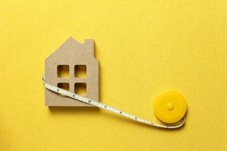 House model with tape measure on yellow fabric background. Buying a house, house size, real estate concept