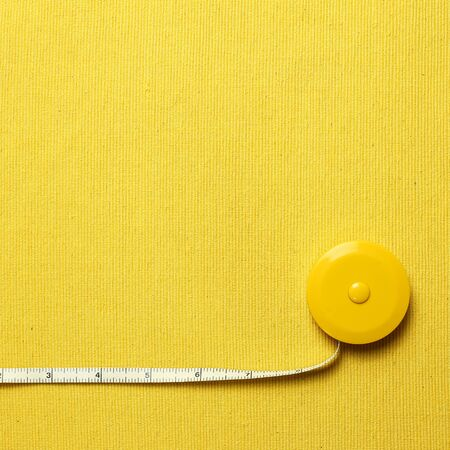 Tape measure on yellow fabric background 写真素材