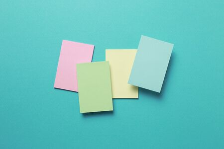 Colorful memo pad, sticky notes on mint background