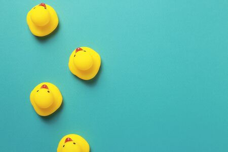 Yellow rubber duck doll on mint blue background