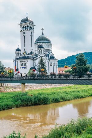 The Holy Trinity Orthodox Cathedral and river in Sighisoara, Romania Stock Photo