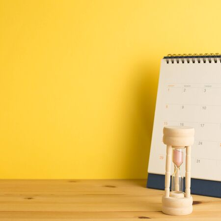 Calendar and hourglass on table, Business schedule and time concept Banco de Imagens