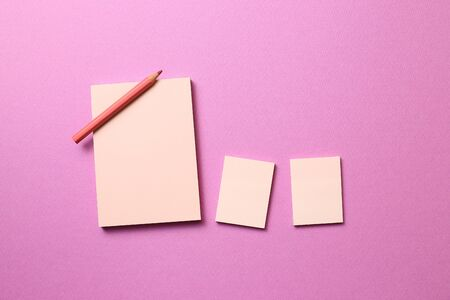 Pink memo note pad and pink colored pencil on pink background