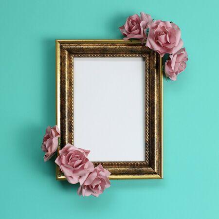 Empty antique photo frame with rose decoration on green background Standard-Bild