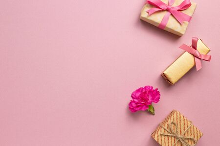 Gift boxes with carnation flower on pink background. Anniversary concept, flat lay, top view, copy space 免版税图像
