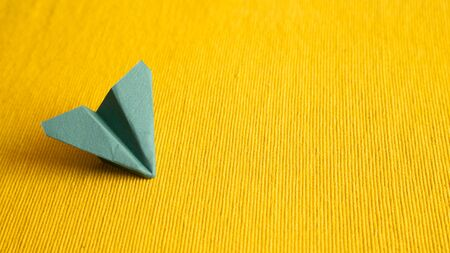 Green paper plane on yellow fabric background. copy space