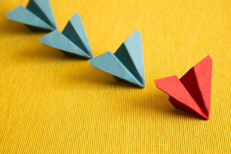 Row of paper plane on yellow fabric background. leadership concept 免版税图像