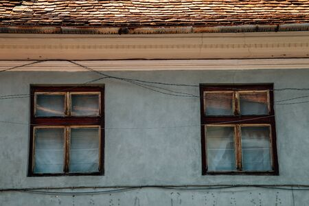 Medieval old house, gray wall and wooden window in Sibiu, Romania