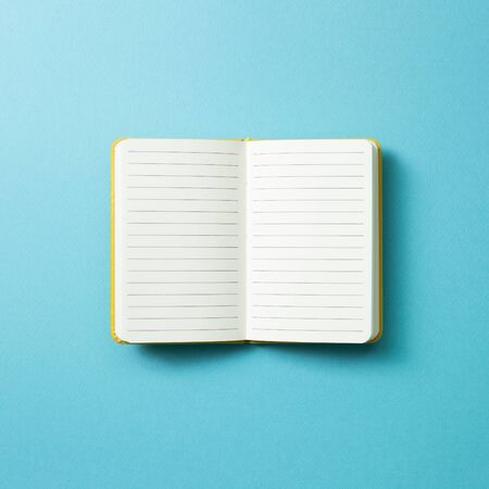 Open empty notebook on blue background. top view, copy space