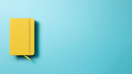 Yellow diary notebook on blue background. top view, copy space